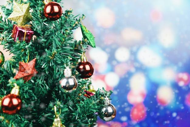 Árvore de natal linda decoração no fundo desfocado colorido bokeh - árvore de natal com estrela de caixa de presente de bola e luzes decoradas pinheiro celebração do festival de férias de ano novo em casa interior