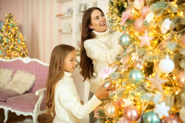 Árvore de natal. mãe e filha decorando uma árvore de natal juntas e parecendo satisfeitas