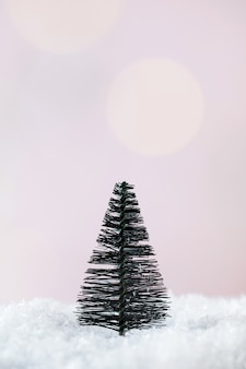 Árvore de natal na neve em um minimalismo de fundo rosa o conceito de ano novo e natal ...