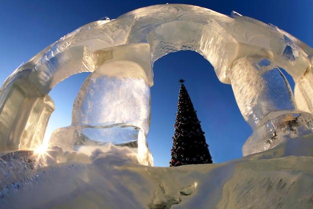 Árvore de natal no fundo da estrutura de gelo ao sol