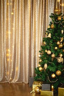Árvore de natal verde abeto artificial na sala dourada com guirlandas de luzes decoradas com bolas douradas, miçangas e brinquedos.