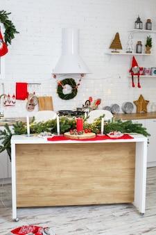 Árvore de natal verde, decorada com bolas, enfeites de natal, guirlandas amarelas. decorações de ano novo na cozinha. ano novo. decorações da casa para o natal.