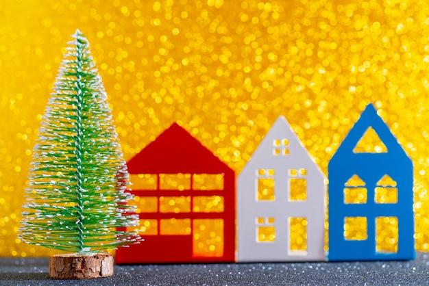 Árvore de natal verde na brilhante. bokeh bonito. pequenas casas.