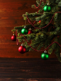 Árvore de natal, vestido de bolas, fica em uma mesa de madeira.