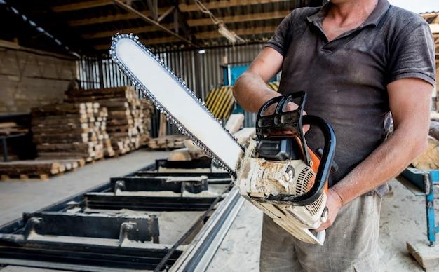 Árvore do corte do lenhador com a serra de cadeia na serração. serraria moderna. indústria serrar tábuas de toras.