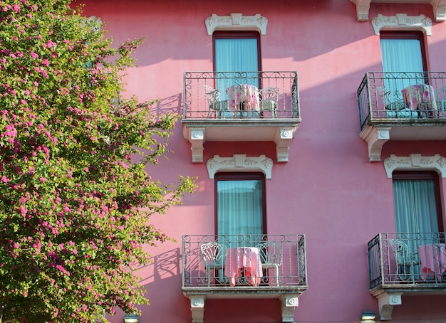 Árvore em flor e linda casa rosa com varandas em sirmione