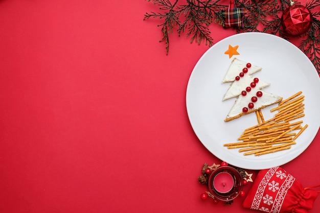 Árvore feita de pão com creme de queijo decorado com frutas num prato branco sobre fundo vermelho.