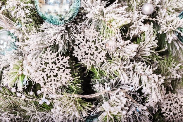 Árvore tradicional de natal ou ano novo decorada com um brinquedo de floco de neve de prata.