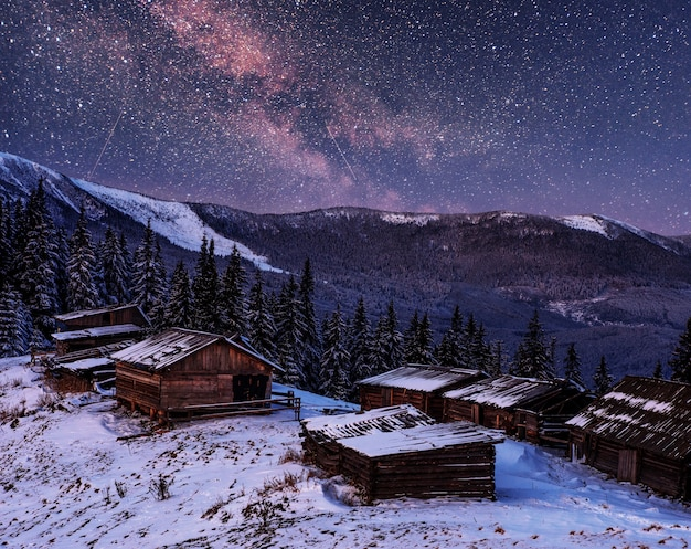Árvores cobertas de neve de inverno mágico e aldeia de montanha. céu noturno vibrante com estrelas e nebulosa e galáxia.