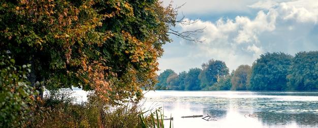 Árvores coloridas de outono à beira do rio, reflexo das árvores no rio, panorama