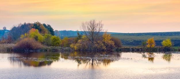 Árvores coloridas de outono refletem-se na água do rio ao pôr do sol