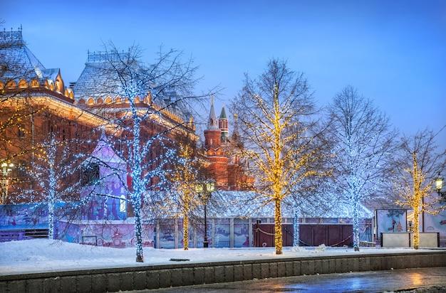 Árvores com guirlandas perto do museu histórico na praça manezhnaya no início da manhã de inverno