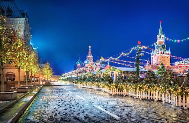 Árvores de ano novo em bolas perto do gum na praça vermelha em moscou e da catedral de são basílio à luz das luzes festivas noturnas