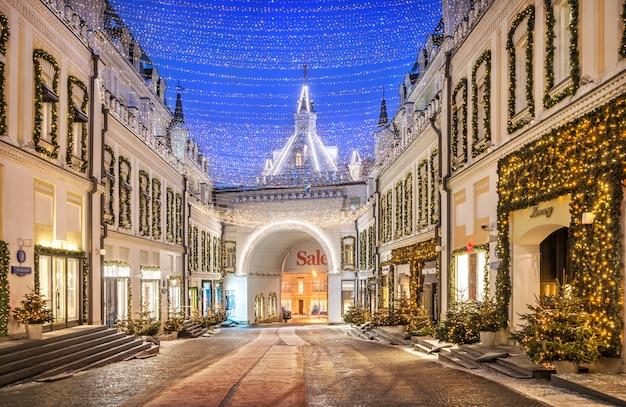 Árvores de ano novo na passagem de tretyakovsky em moscou e boutiques decoradas à luz de uma manhã de inverno