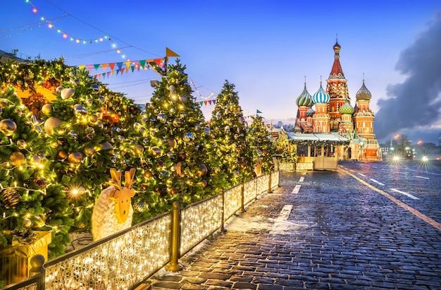 Árvores de ano novo na praça vermelha de moscou, perto da catedral de são basílio, em uma manhã de inverno