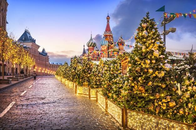 Árvores de natal com bolas na praça vermelha em moscou e na catedral de são basílio em uma manhã de inverno