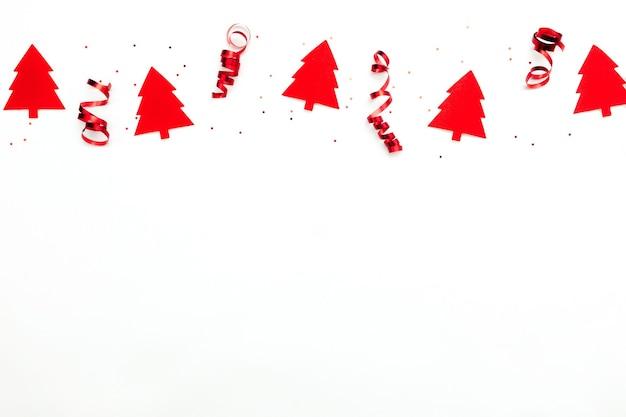 Árvores de natal com fitas vermelhas e estrelas de brilho em fundo branco.