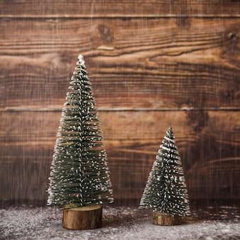 Árvores de natal de ornamento entre a queda de neve