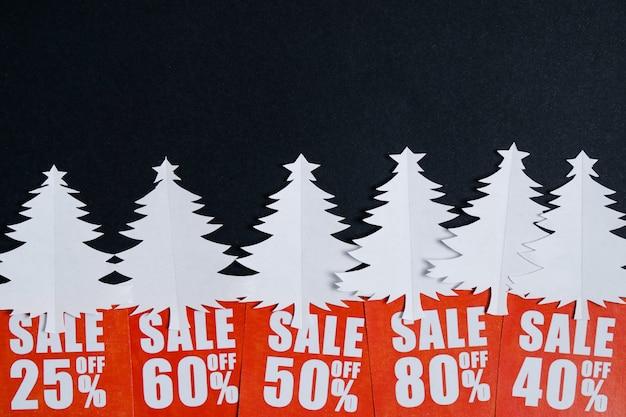 Árvores de natal de papel com cartões de desconto vermelho