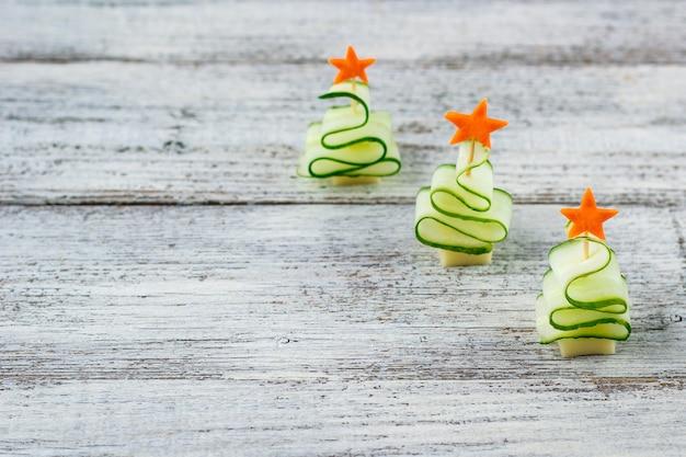 Árvores de natal de pepino e queijo com estrela de cenoura