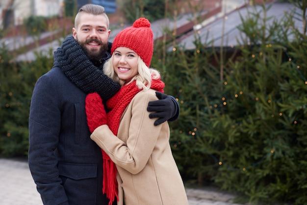 Árvores de natal frescas e jovem casal