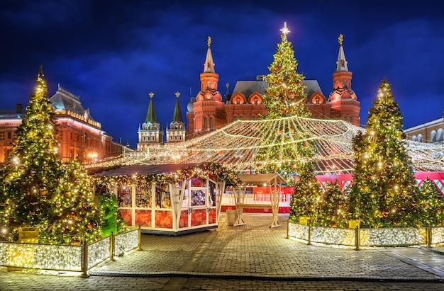 Árvores de natal na praça manezhnaya e o museu histórico com iluminação noturna