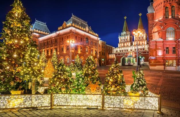 Árvores de natal na praça manezhnaya em moscou, perto do portão da ressurreição, e decorações para árvores de natal com iluminação noturna