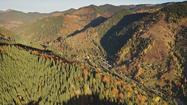 Árvores de outono sol no topo das montanhas ninguém paisagem da natureza na estrada rural em casas de campo em
