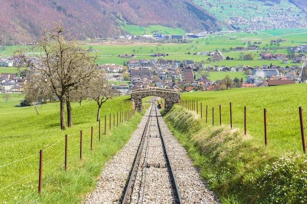 Árvores e ferrovia no sopé do monte. stanserhorn na suíça no início de maio