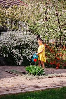 Árvores floridas e arbustos no jardim de primavera uma menina rega plantas de um regador de jardim em um ...