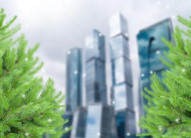 Árvores perenes em fundo de cidade grande nevando