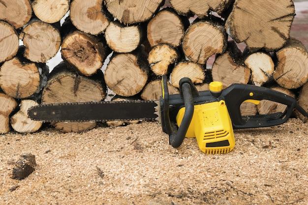 Árvores serradas e uma serra elétrica. ferramenta elétrica para processamento de madeira.