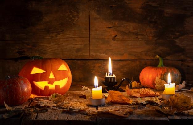 As abóboras de halloween dirigem a lanterna do jaque o na tabela de madeira em uma floresta místico na noite.