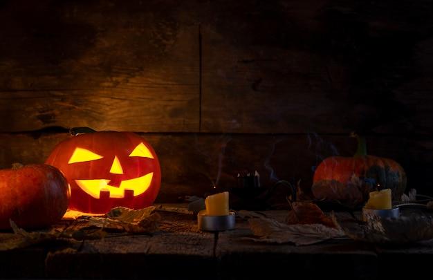 As abóboras de halloween dirigem o jaque o lanterna na tabela de madeira.