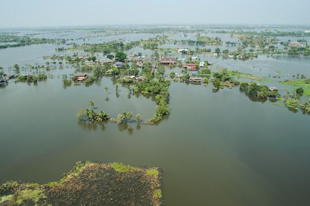 As águas da enchente ultrapassam uma cidade na forma de tailândia acima da vista