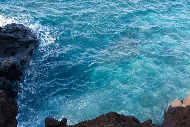 As águas límpidas e azuis do oceano atlântico e a lava resfriada. ilha lanserote, espanha.