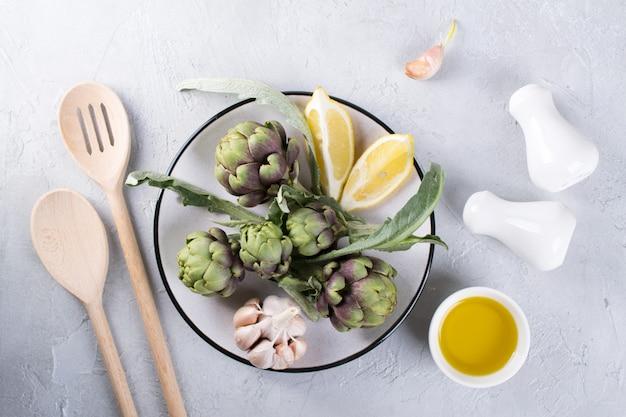 As alcachofras cruas maduras verdes dirigem prontas para cozinhar. alcachofras e ingredientes alho, limão e azeite