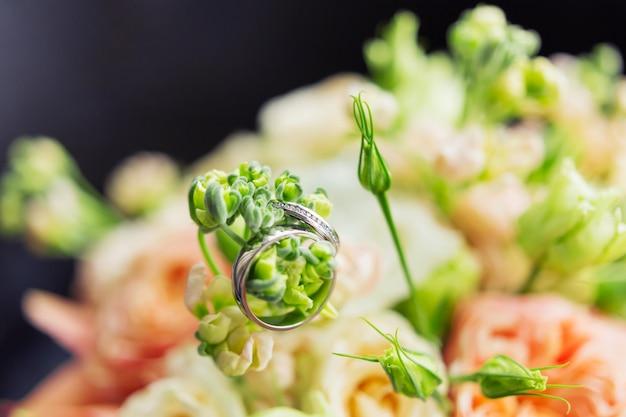 As alianças de casamento douradas com diamantes encontram-se dentro do ramalhete nupcial.