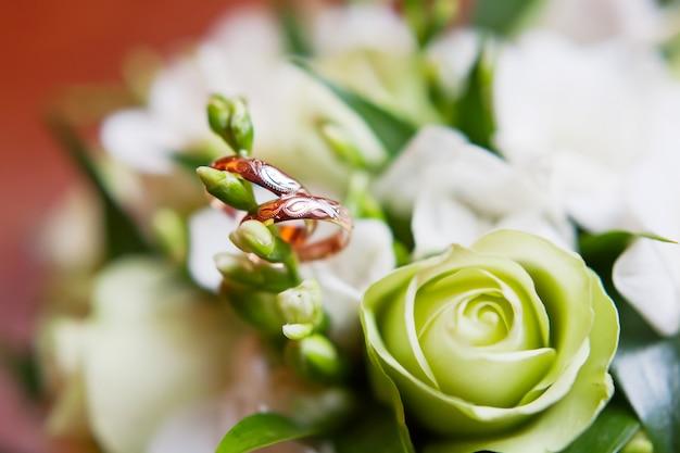 As alianças de casamento douradas com ornamento encontram-se dentro da flor no ramalhete.