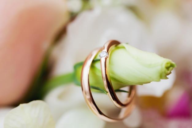 As alianças de casamento douradas com ornamento encontram-se na flor no ramalhete da noiva.
