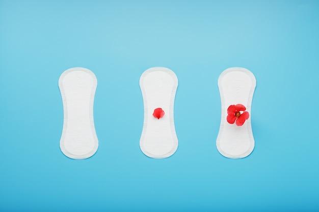 As almofadas sanitárias das mulheres no azul. o conceito de dias críticos, ciclos menstruais em várias etapas.