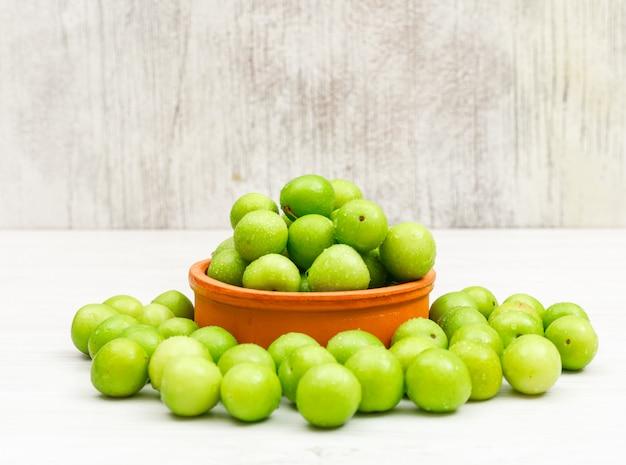 As ameixas verdes orvalhadas em uma argila redonda rolam no branco e no grunge, vista lateral.
