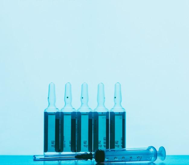 As ampolas com solução de injeções e seringa descartável em um contexto azul