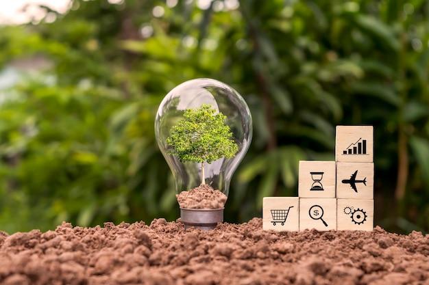 As árvores crescem em lâmpadas economizadoras de energia e blocos de madeira com símbolos comerciais. conceito financeiro empréstimos e investimentos em energia