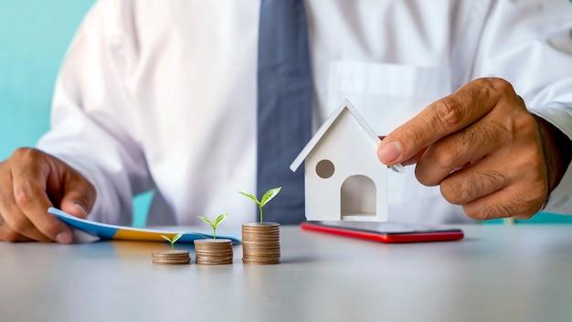 As árvores crescem em pilhas de moedas e os investidores apertam as mãos com conceitos de finanças domésticas, hipotecas, imóveis e empréstimos hipotecários.