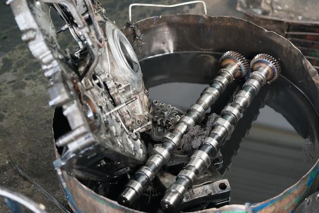 As árvores de cames e a tampa da válvula do motor de um carro embebem-se em um balde de óleo sujo.