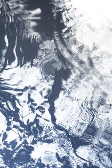 As árvores lançam sombras borradas na água lisa e ondulada. fundo abstrato borrado.