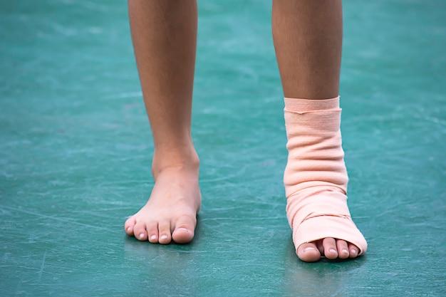 As ataduras de gaze ao redor do tornozelo menino e perna inchaço de inflamação
