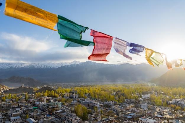 As bandeiras de oração coloridas com vista para a paisagem da cidade de leh no outono