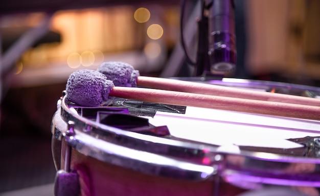 As baquetas estão no tambor. batedores para tímpanos. fundo colorido bonito.
